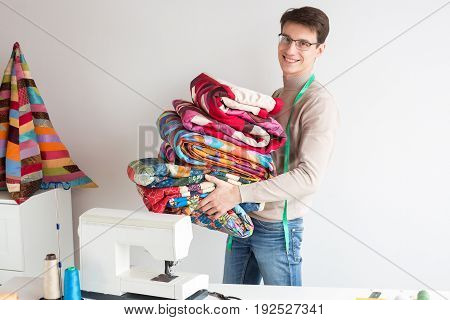 quilting and patchwork at workshop of tailor male - smiling tailor in glasses with a stack of stitched fabrics is near the desktop with a sewing machine, the neck hangs tailor measuring tape