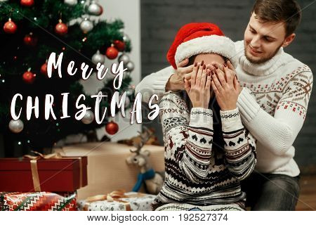 Merry Christmas Text Sign Greeting With Happy Family Couple, Handsome Man Preparing A Christmas Pres