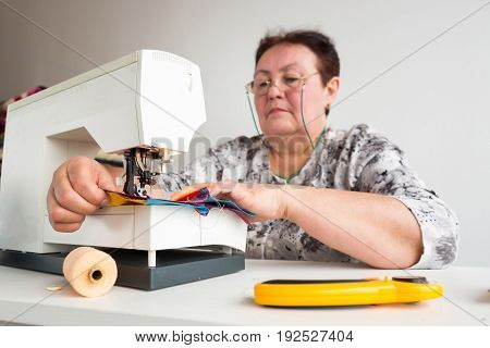 patchwork and quilting - tailor sews on the sewing machine multicolored patchwork fabric sitting at a white table, on which are threads, buttons and rotary fabric cutters on white background.