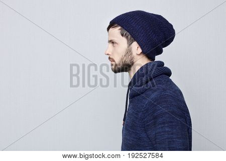 Sideways portrait of natural brunette Caucasian man wearing warm clothes on white background. Bearded hipster with clean shaved temples and stylish well-trimmed moustaches looking serious and brutal at copy space for your advertising.