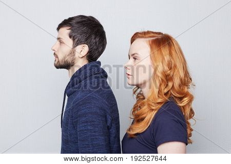 Trust and devotion concept. Redhead freckled Caucasian woman is looking the same direction as her muture brutal brunette handsome boyfriend. Young couple posing in white studio background with serious face expressions.