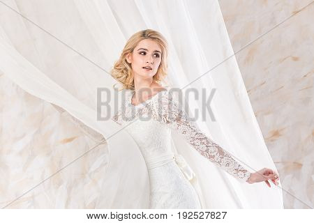 fashionable gown, beautiful blonde model, bride hairstyle and makeup concept - young pretty lady in wedding white dress standing indoors on light background, charming woman posing near curtains