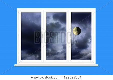 window with view to Moon on the dark cloudy evening sky