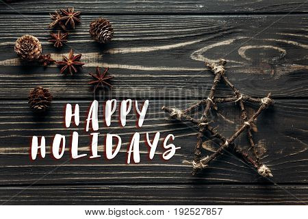 Happy Holidays Text Sign On Stylish Simple Star And Anise And Pine Cones On Rustic Wooden Background