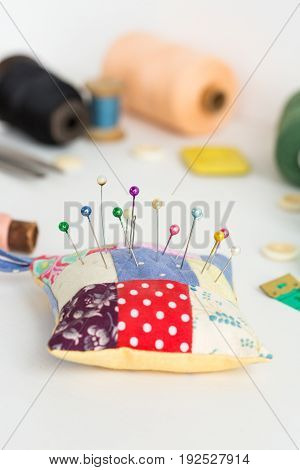 needlework, craft, sewing and tailoring concept - close-up on white desk with pincushion and pins, measuring meter, pink, blue and black thread spools, white buttons, soap, selective focus, vertical