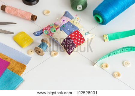 needlework, craft, sewing and tailoring concept - tools closeup on white desk, measuring meter, thread spools, soap, pieces of colorful patchwork fabric, pincushion, buttons, scissors