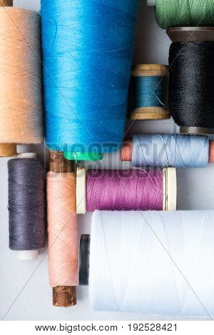 tailoring, sewing, patchwork and concept - closeup on blue, white, black, apricot, pink, purple and green color threads in new bobbins on white background at workshop, top view, flat lay