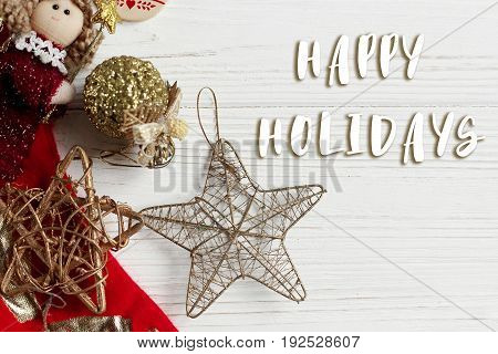Happy Holidays Text Sign On Christmas Golden Star And Toys And Red Stockings On White Rustic Wooden