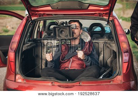 Behind Scene Improvisation. Cameraman From Trunk Of Car Shooting Film