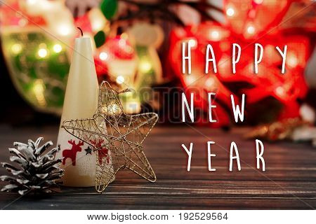 Happy New Year Text Sign On  Christmas Candle And Toys On Background Of Garland Lights On Black Rust