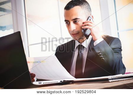 Young And Confident Businessman Working At Table In His Office