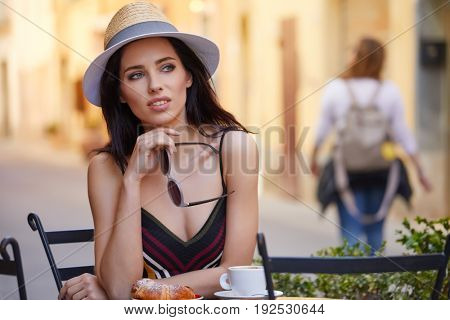 woman having italian coffee at the cafe on the street in Toscana city. Soft focus with small depth of field