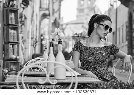 woman sitting at the cafer on the famous street with local food markets in Italy city. BW concept