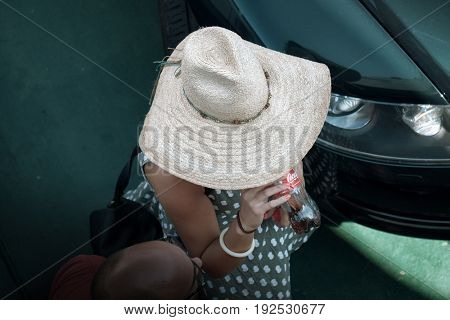 VILLA SAN GIOVANNI, ITALY - AUGUST 10, 2016: high view of a lady with straw hat is drinking from a plastic bottle of Coca-Cola supported by hand with pink nail polish
