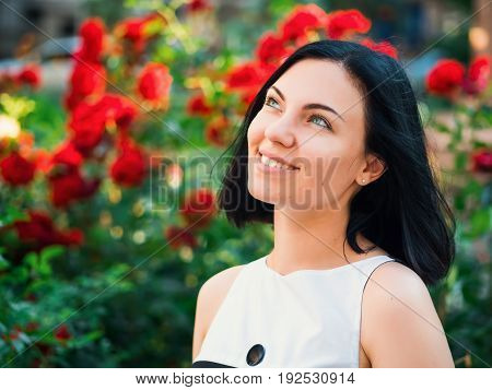 Beautiful young woman on a background of red flowers. The concept of beauty and health. Beautiful fashion girl, sweet and sensual.