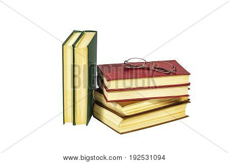 A pile of hard-bound book and reading glasses lie on a light background