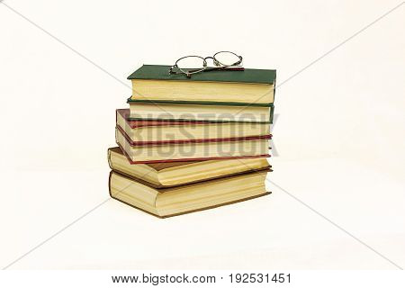On the white surface is a pile of hard-bound book and reading glasses