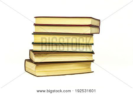 A stack of several hard-bound books rests on a light surface
