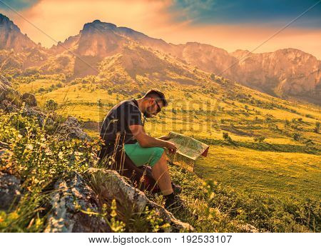 A hiker studying the map while on the path at the dusk in the misty Apuseni Mountains in Transylvania Romania.