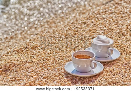 Two coffee cups, Espresso and Cappuccino at the Sea Shore on the Beach