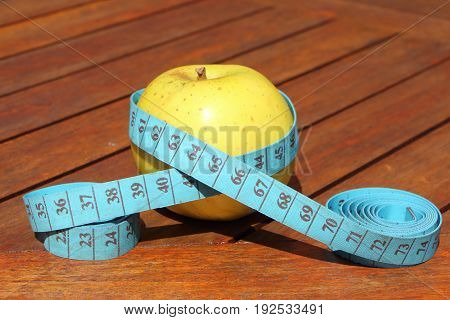 Tape measure around an apple on a table