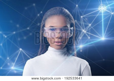 Future technology concept. Waist up portrait of serious young mulatto woman standing in front of futuristic touchscreen interface