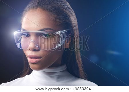 Futuristic style. Portrait of confident young mulatto woman wearing shiny eyeglasses. Copy space