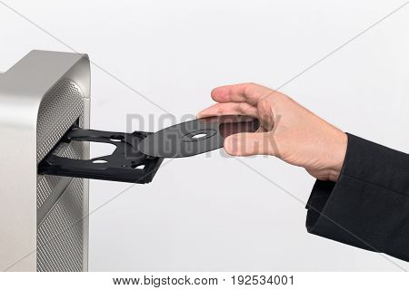 Inserting a black CD / DVD into a computer. Hand insert. On white background poster