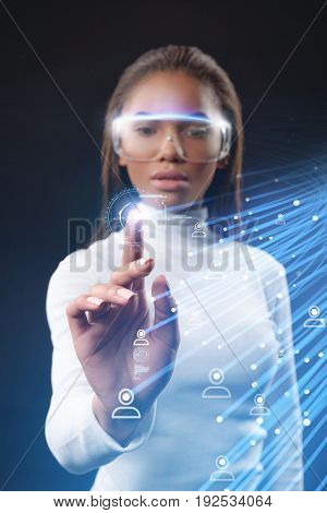 Serious young mulatto girl touching future technology social network button
