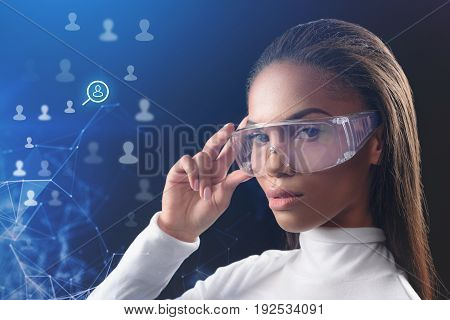 Connecting to internet by power of thought. Attractive young african woman is touching special futuristic eyewear and looking at camera with seriousness