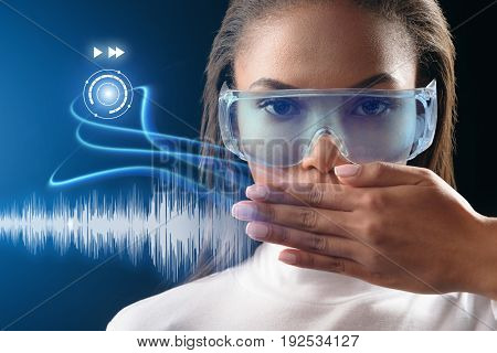 Future computer technology instead of real speaking. Confident young woman is closing her mouth by hand. Virtual media signs appear