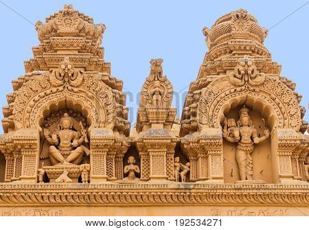 Nanjangud India - October 26 2013: Double Niche in beige elaborately decorated sandstone at Srikanteshwara Temple showing both statue of Lord Shiva. Sexual imagery nearby.