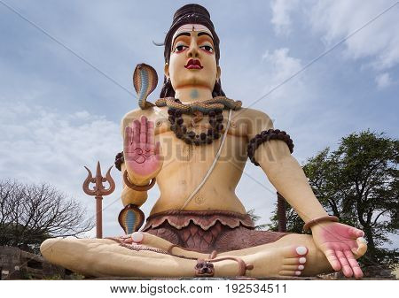 Nanjangud India - October 26 2013: Isolated and frontal shot of giant Lord shiva statue off Srikanteshwara Temple against blue sky with white clouds. Multicolor and with cobra snake named Vasuki.