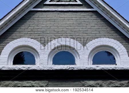 Half round attic windows in a gray brick house