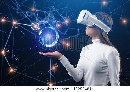 Whole world is on my palm. Joyful young african girl is watching 3d virtual reality headset. Abstract globe and internet lines over her hand