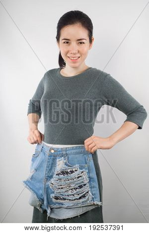 young woman be pregnant in maternity clothes try to wear short jean on gray cement wall background.