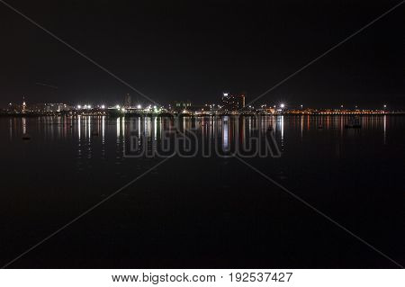 Boston Massachusetts USA - November 3 2016: Lights from East Boston reflecting off Boston harbor before sunrise