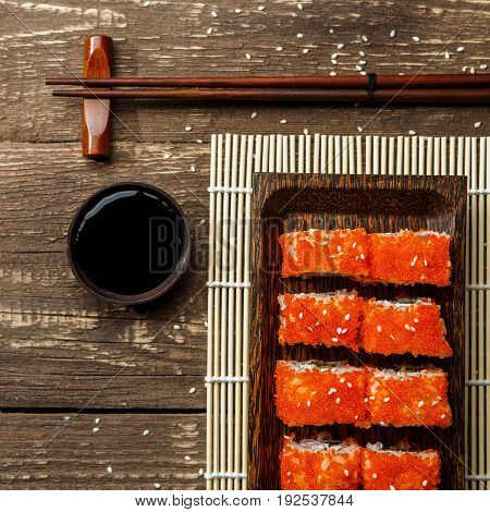 Photo rolls on rectangular plate, black chopsticks, soy sauce on wooden table