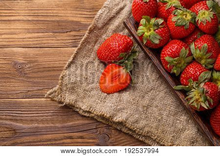 Ripe strawberry on wooden plate at linen cloth and table
