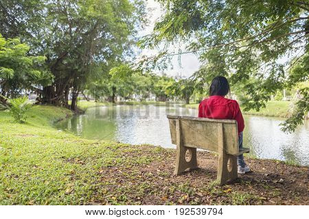 Girl sit alone in the garden looking fish in lake