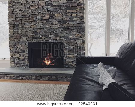 girl relaxing on the couch with feet up by the fireplace