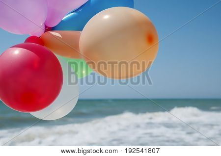 Multicolored balloons against the background of the sea and blue sky