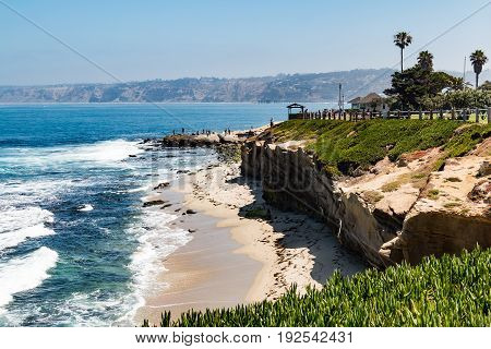 LA JOLLA, CALIFORNIA - JUNE 16, 2017:  Ice plants on a cliffside at La Jolla Cove in San Diego, California, with people enjoying the view from an observation point.