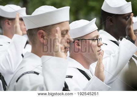 Participating U.S. Navy personnel raise their hands to be sworn in during the re-enlistment and promotion ceremony at the National September 11 Memorial site. Fleet Week, NEW YORK MAY 26 2017