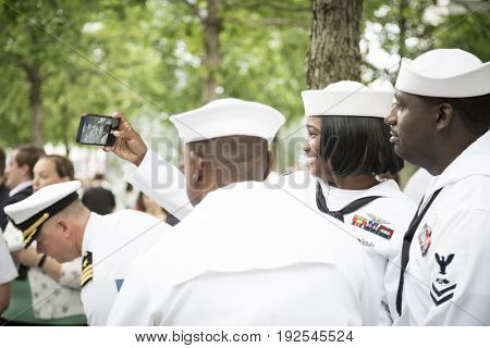 Participating U.S. Navy sailors pose for a photograph together after the re-enlistment and promotion ceremony at the National September 11 Memorial site. Fleet Week, NEW YORK MAY 26 2017