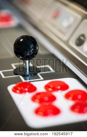 Detail of a black joystick and red buttons on an arcade game machine