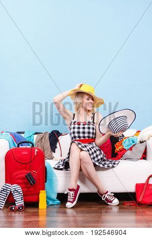 Packing problems necessary things during the trip concept. Woman sitting on sofa holding sun hat getting ready for vacation choosing clothes to pack into suitcase