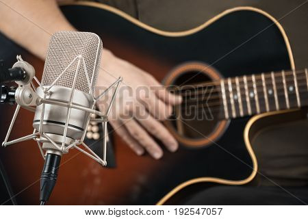 Microphone Recording An Acoustic Guitar Played By Hand