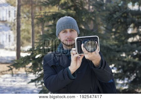 The guy with the camera in the winter forest, making a shot