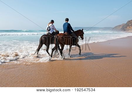 Horse riding at the beach at the atlantic ocean